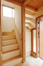 階段の間から光が差し込む玄関ホール